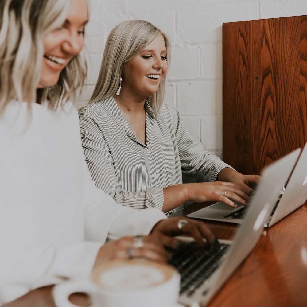 Zwei Frauen benutzen Laptops